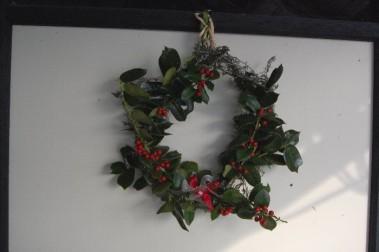 庭のクリスマスホーリーで作ったリースをドアに飾る