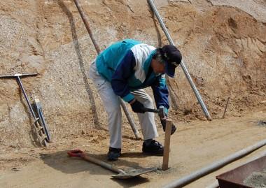 掘った柱の穴底にセメントを入れて叩き固める