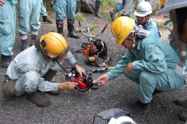 山林の作業現場でチェンソーのエンジン調整