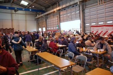 大きなシャッターと天井クレーンのある整備工場の中が食堂になっていた