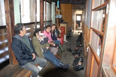ここで待ちます、足元には食べている人の靴が並ぶ