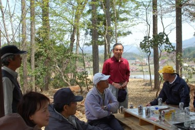 里山まなぶ会の吉さんの進行でまずま屋完成を祝っての花見が始まる