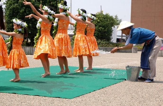 焼けた砂利舗装の上で踊るフラガールに打ち水をする優しいオジサン