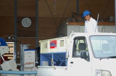 YOSIさんが倉庫の定位置に車を停めて籾を乾燥機に張込む