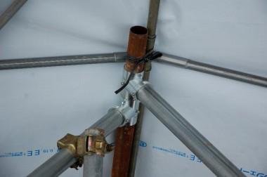天井に紐で固定した足場単管に固定金具を通す