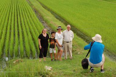 田んぼを背景にお父さんが家族を写しています 2