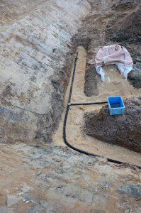 モミガラを5㎝厚さに敷いてその上に穴開き集水パイプを置く、青い箱方向に排水